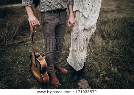 Stylish Hipster Couple Holding Hands Closeup In Windy Field. Boho Gypsy Woman And Man With Guitar  H