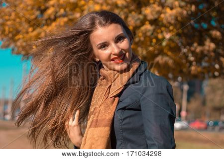 girl stands in the Park in the Sun and her hair fly away with the wind