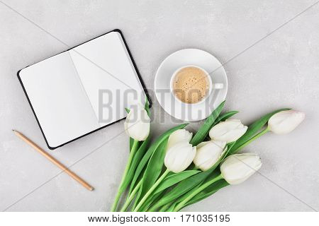Woman working desk with coffee mug notebook and spring tulip flowers top view in flat lay style.