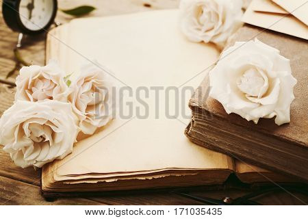 Retro still life with pale rose flowers and open ancient book. Nostalgic composition on old wooden table.