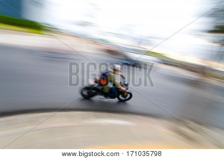 Biker rides a moped. High speed. Blurring background.
