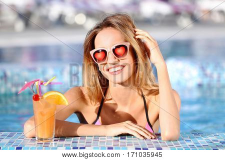 Young beautiful woman wearing sunglasses with hearts in swimming pool