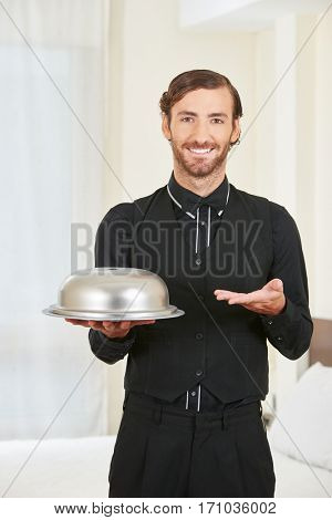 Hotel page serving food with cloche on a tablet in a hotel room