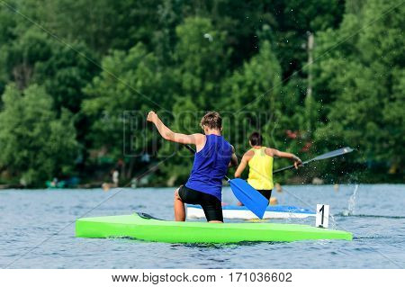 two young men rowers canoeists paddling on lake rowing competitions