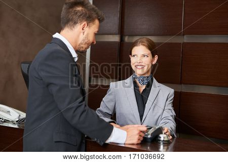 Businessman paying with credit card in hotel at the reception during check-out
