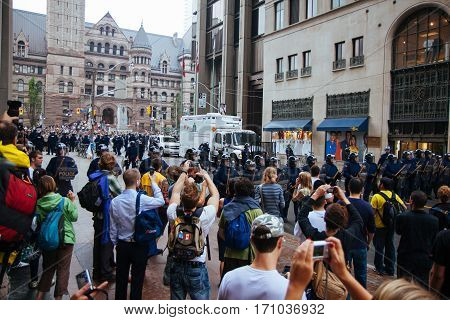 TORONTO, CANDA - JUNE 26, 2010: RCMP officers blcok two separate groups of protestors from joining up with another, larger group of protestors.
