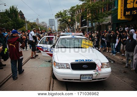 TORONTO, CANDA - JUNE 26, 2010: Protestors and onlookers surround a police car on Queen St. West that was vandalized