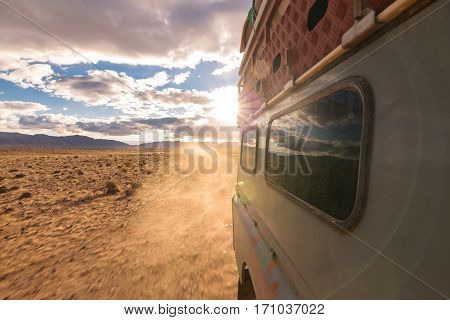 View from the side window of a four by four oldtimer while driving off-road on a dusty road in a stone desert in Morocco.
