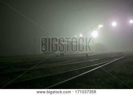 Gloomy railway at night in the fog