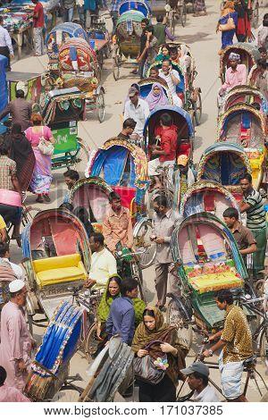 DHAKA, BANGLADESH - FEBRUARY 22, 2014: Rickshaws transport passengers in Dhaka, Bangladesh. About 500 000 rickshaws daily cycle in Dhaka nicknamed