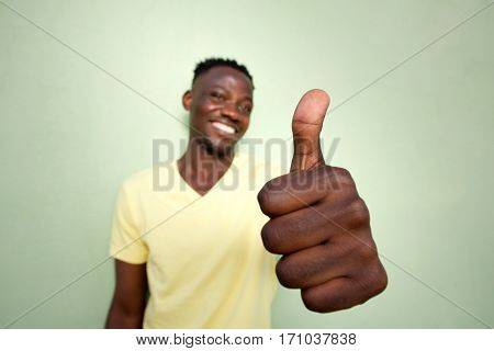 Young Black Man Gesturing Thumbs Up Sign By Green Wall