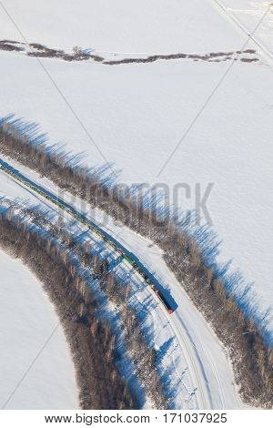 freight train running on railway in snow covered plain, aerial view