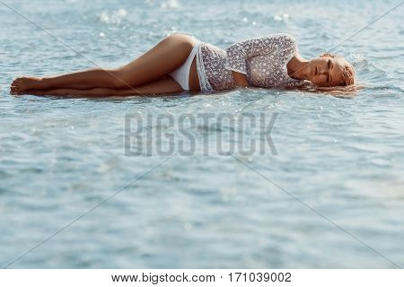 Girl in white transparent dress and bikini lies in water on sea background. Her hair is wet.