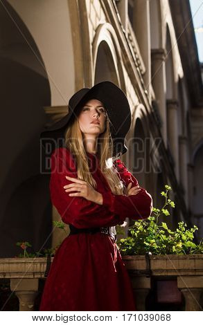 Girl portrait in red dress and broad black hat on building background. She crossed her arms over chest and looks away.