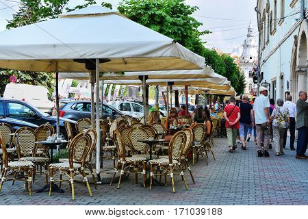 CLUJ-NAPOCA ROMANIA - AUGUST 18 2012: Tourists on sightseeing tour on the streets of old town. outdoor terrace on the sidewalk with sun protecting umbrellas.