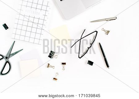White office desk frame with paper blank and supplies. Laptop notebook scissors pen clips glasses and office supplies on white background. Flat lay top view mockup.