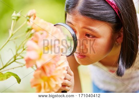 Girl with magnifying glass explores nature as reseracher