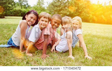 Happy group of kids have fun in summer in meadow