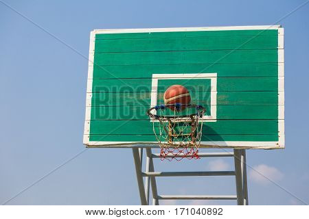 basketball fast moving into the basket at an outdoor field on a clear sunny day