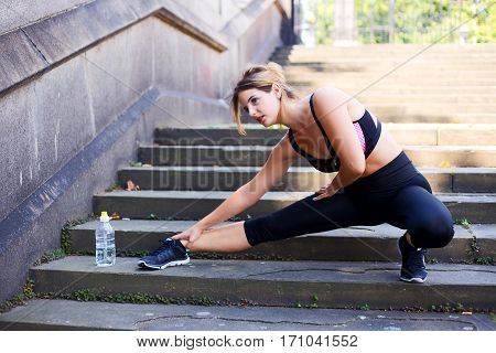 a fitness girl stretching her leg muscles