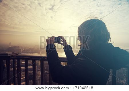 Zoung woman taking photos from the rooftop of St Paul's Cathedral on a foggy day in London, UK - city break - tourism concept