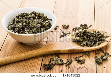 Bowls With Dry Green Tea, Scattered Leafs On Table