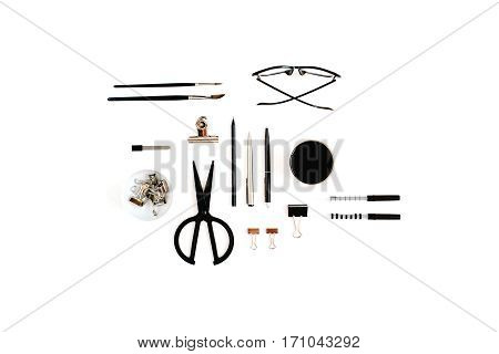 White office desk with supplies. Coffee scissors pen clips glasses and office supplies on white background. Flat lay top view office table desk.