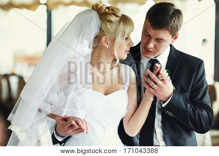 Fiance Holds Bride's Hands Tenderly While Hugging Her