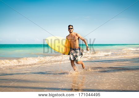 Surfer beach lifestyle people - man surfing running with with bodyboard in water on tropical beach