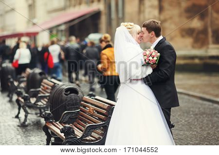 Just Married Couple Kiss Standing Behind The Benches On The Street
