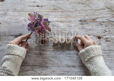 Female hands decorating with flowers and letters over wooden background