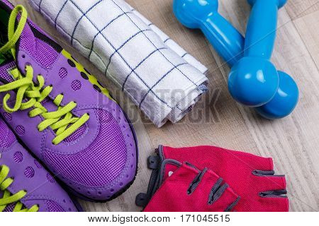 Fitness gym equipment. Sneakers, dumbbells with towel. Workout gloves and footwear. Sport trainers with green shoelace.