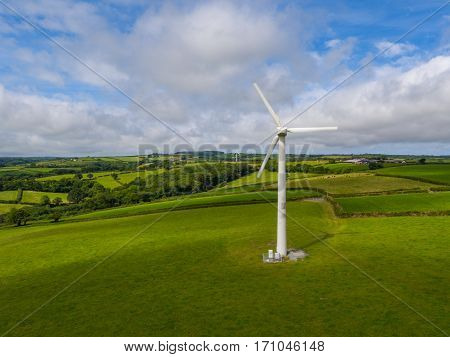 aerial view of a electricity generating wind turbine in green field