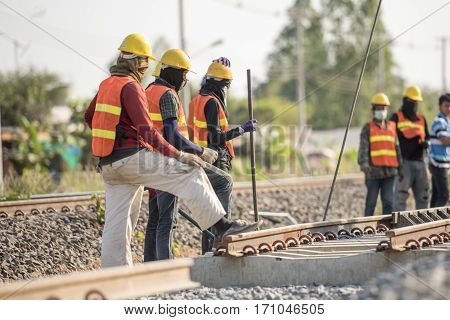 Construction team work in standard construction safety uniform installing precast concrete railway in mega project construction site