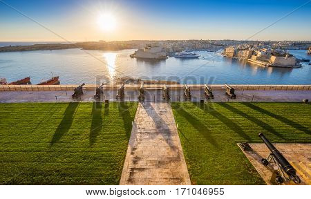Valletta Malta - Beautiful sunrise at the famous saluting battery of Valletta with Grand Harbor and Senglea and Brigu at background. Blue sky and sunlight.