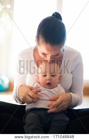 Beautiful mother in white t-shirt holding her cute baby son, sitting in her lap, kissing him.