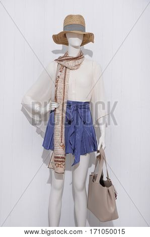 female clothing with hat and scarf on mannequin-wooden background