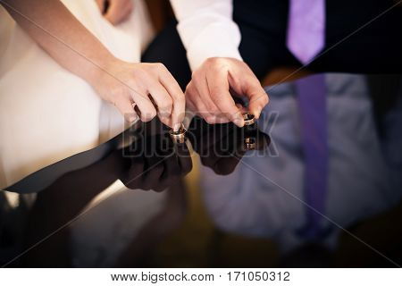 The bride and groom take wedding rings from the mirror surface
