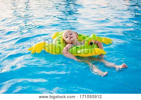 Cute little girl relaxing in swimming pool, floating with inflatable ring. Active summer vacation on the beach.