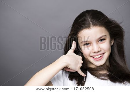 Sign Call me. Pretty brunette litte girl, isolated on gray background