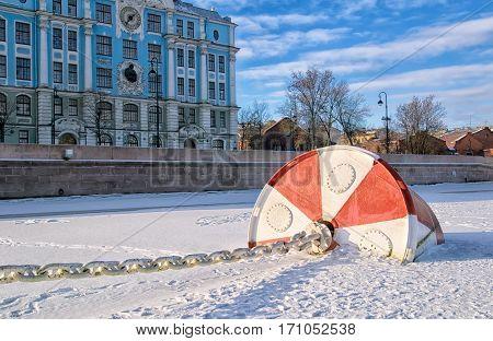 SAINT-PETERSBURG, RUSSIA, FEBRUARY 10, 2017: View of the frozen Neva River with float of The Cruiser Aurora near Petrogradskaya Embankment. On the background is Nakhimovskoye Naval College