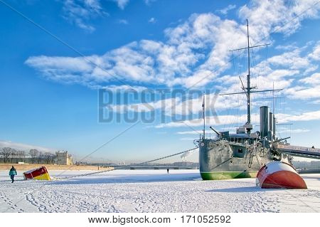 SAINT-PETERSBURG, RUSSIA, FEBRUARY 10, 2017: People walk on the ice of The Neva River near Cruiser Aurora on sunny day. On the background is The Liteyny Bridge