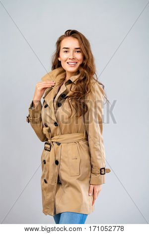 Portrait of a young woman without make-up. Beautiful brunette model in beige coat