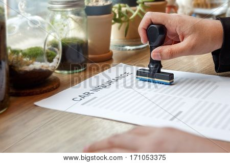 Hands holding approved rubber stamp with car insurance on wooden desk