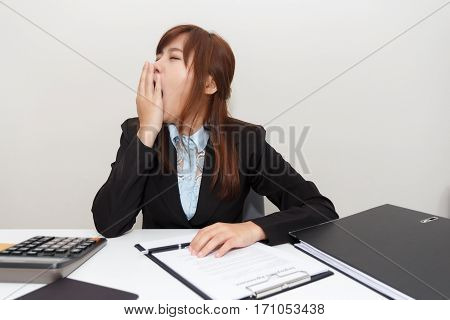Businesswoman yawn or feel sleepy while working at office after having lunch