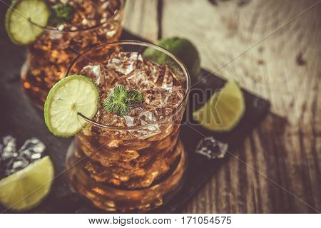 Rum and cola cocktail in glasses, rustic wood background