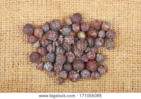 Dried juniper seed on textured burlap background