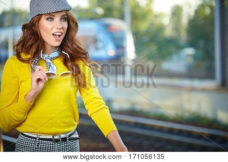 pretty adult woman with a suitcase near the train on the platform.