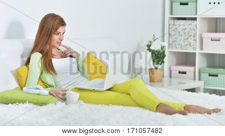 young beautiful woman relaxing in bed at home, using laptop