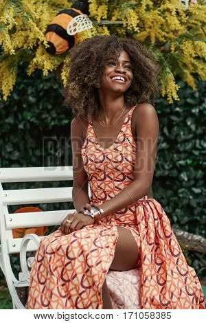 Curly-haired young afro american girl sitting on a wooden white bench. Plant background